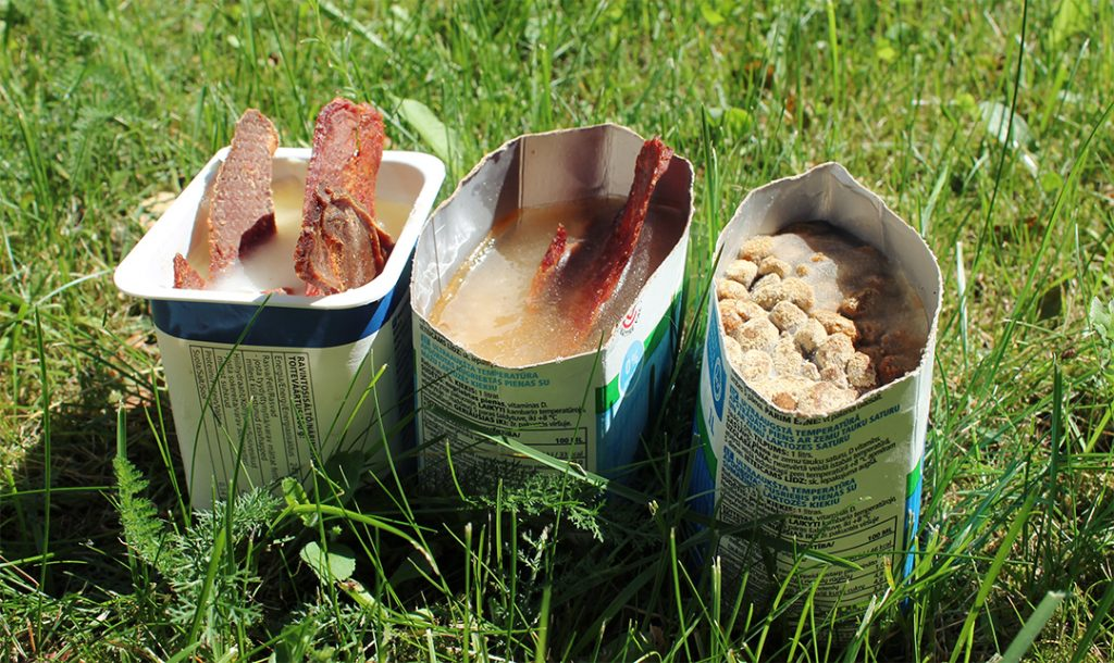 Kolme erilaista jäädytettyä koiran jäätelöä, jotka ovat vettä ja herkkupaloja jäädytettynä puolikkaissa maitopurkeissa.